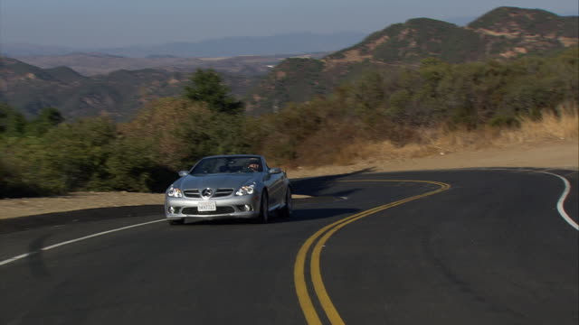 vehicle pov, ts ms of silver mercedes-benz convertible car driving along forested mountain road /malibu canyon road, california, united states - mercedes benz stock videos and b-roll footage