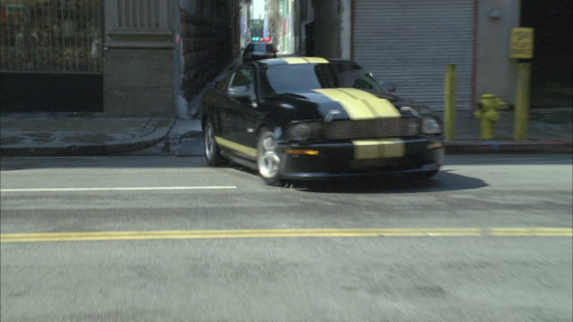 ds, ha, vehicle speeding away from chasing police car through alley onto city street, los angeles, california, usa - 追いかける点の映像素材/bロール