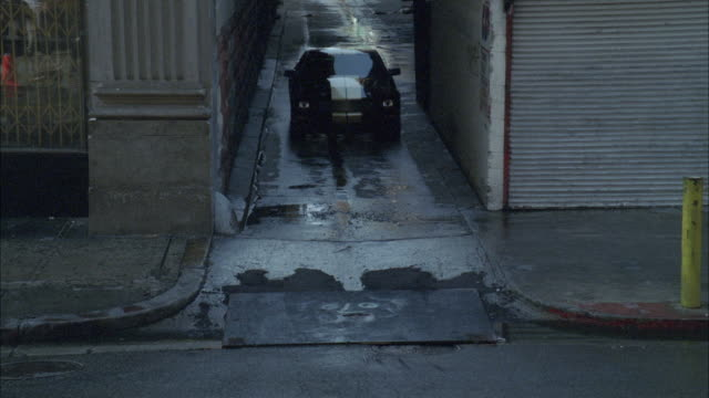 DS, HA, vehicle speeding away from chasing police car through alley onto city street, Los Angeles, California, USA