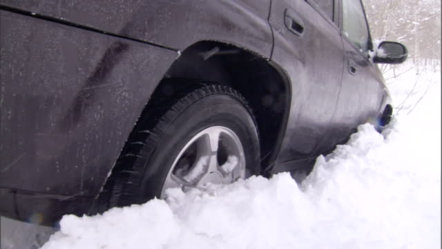 a vehicle spins its wheels in the snow. - bloccato video stock e b–roll