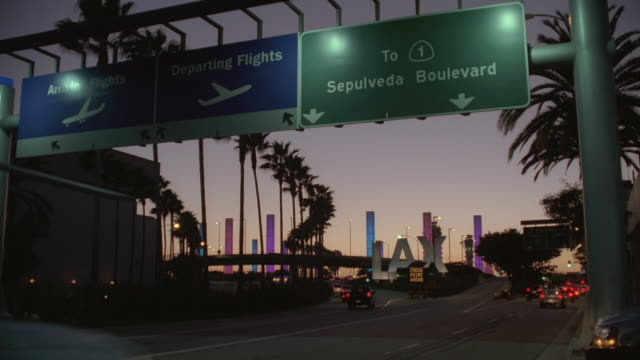 stockvideo's en b-roll-footage met ws vehicle traffic traveling past lax airport signs / los angeles, california, united states - letterbox format