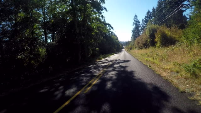 a vehicle traveling on a rural road in the san juan islands during a warm summer day near lime kiln state park. - coastal road stock videos & royalty-free footage