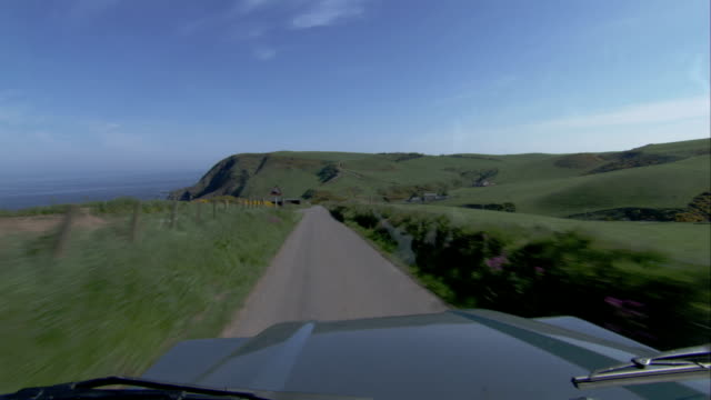 a vehicle travels down a narrow road in the highlands of aberdeenshire scotland. available in hd. - クロヴィー点の映像素材/bロール