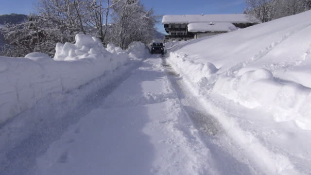 A vehicle travels in ruts on a snow-covered road near a chalet in the Alps.