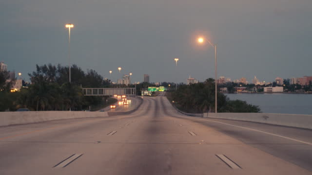 vidéos et rushes de a vehicle turns off the interstate and enters miami beach, florida. - ressortir