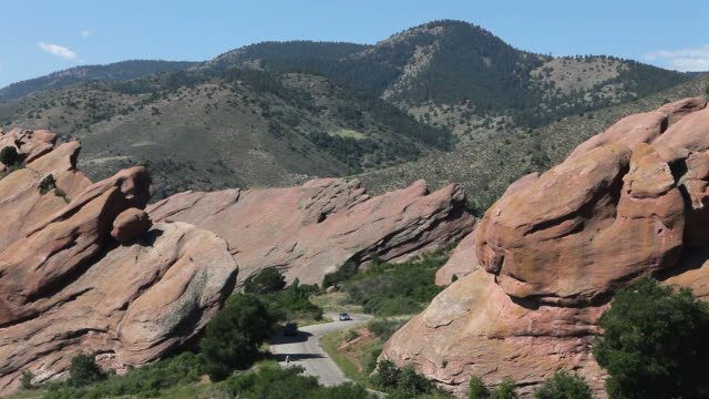 vehicles and bicyclist in red rocks state park, colorado - red rocks stock videos & royalty-free footage