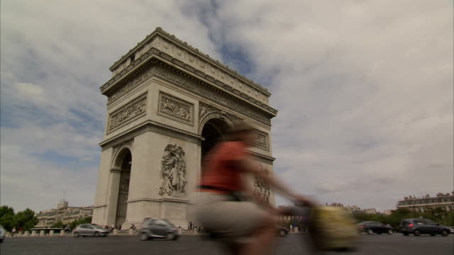 Vehicles and bicyclists drive around the Arc de Triomphe in Paris. Available in HD.