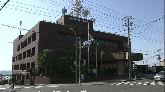vehicles and pedestrians move past the oshima town hall. - local government building stock videos & royalty-free footage