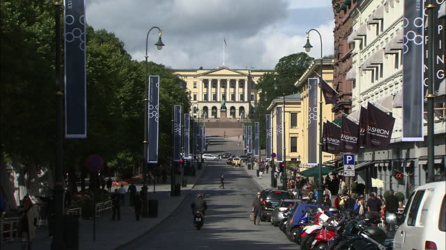Vehicles are parked in front of shops in Oslo, Norway.