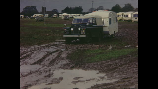 vehicles attempting to exit a muddy field after a caravan rally in england, circa 1968 - land rover stock videos & royalty-free footage