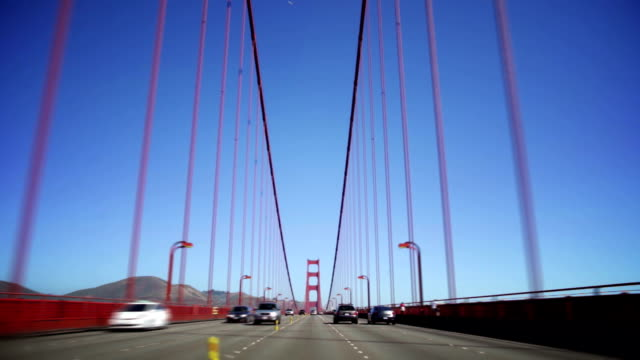vídeos de stock, filmes e b-roll de vehicles commute across the golden gate bridge during the day. - golden gate bridge