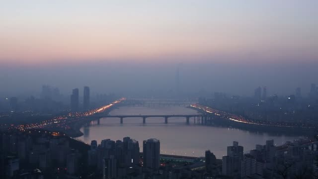 vehicles cross bridges as commercial and residential buildings shrouded in haze stand on the banks of the han river in seoul south korea on thursday... - river han stock videos & royalty-free footage
