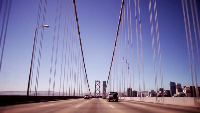 vehicles drive across the bay bridge in san francisco. - san francisco oakland bay bridge stock videos and b-roll footage