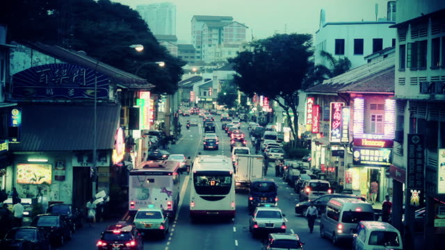 Vehicles drive along the city streets of Singapore at dusk.