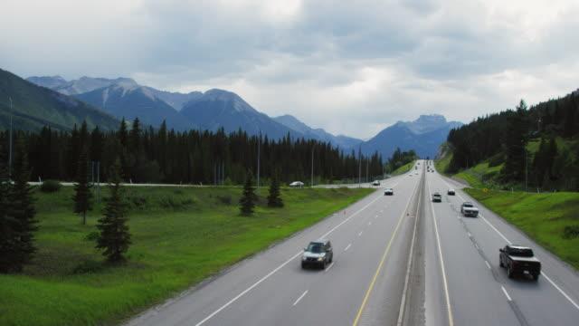 vidéos et rushes de véhicules conduire le long de la route transcanadienne sous un ciel couvert avec des forêts et les rocheuses canadiennes dans l'arrière-plan en alberta, canada - eco tourism