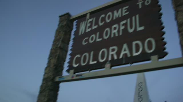 "vehicles drive by the ""welcome to colorful colorado"" state line sign on the colorado/utah border on interstate 70 at sunset - welcome sign stock videos & royalty-free footage"