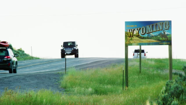 vehicles drive by the wyoming state line sign on the wyoming/colorado border at sunset - general view stock videos & royalty-free footage