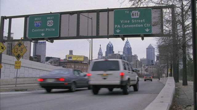 vehicles drive down a freeway near the philadelphia convention center exit. - exit sign stock videos & royalty-free footage