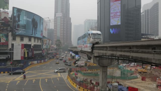 Vehicles drive on an elevated road past the Kuala Lumpur Railway Station as buildings in the background stand shrouded in haze in Kuala Lumpur...