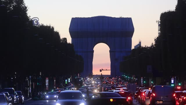 vehicles drive on the avenue des champs elysees, in the background, the project by the artists christo and jeanne claude wrapped arc de triomphe seen... - atmosphere filter stock videos & royalty-free footage