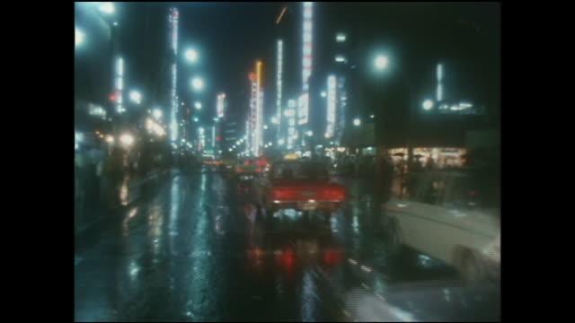vehicles drive on wet pavement  on shinjuku street. - 1970~1979年点の映像素材/bロール