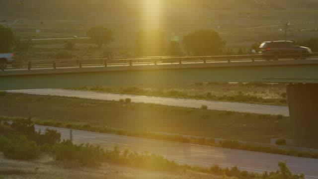 vidéos et rushes de véhicules conduire sur et sous un passage inférieur métallique au coucher du soleil / lever de soleil dans un paysage désertique - ingénierie