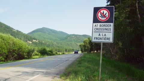 """fahrzeuge fahren an einem """"no marijuana at border crossings sign"""" auf englisch und französisch an einem sonnigen tag vorbei, umgeben von forest und den kanadischen rockies in british columbia, kanada - law stock-videos und b-roll-filmmaterial"""