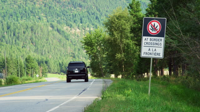 """vehicles drive past a """"no marijuana at border crossings sign"""" in both english and french on the side of the road surrounded by forest and the canadian rockies in british columbia, canada on a sunny day - legalisation stock videos & royalty-free footage"""