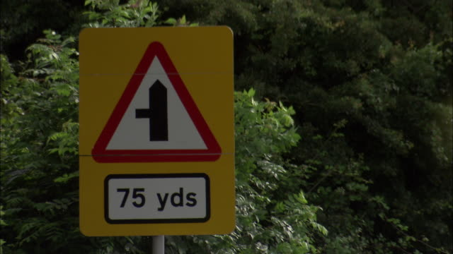 Vehicles drive past junction sign on road, UK
