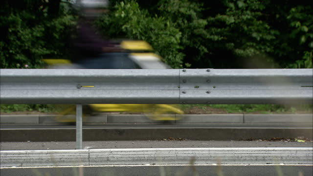vehicles drive past on motorway, uk - städtischer verkehrsweg stock-videos und b-roll-filmmaterial