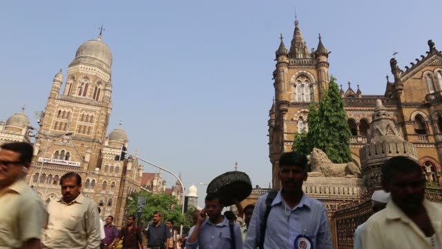 vídeos de stock, filmes e b-roll de vehicles drive past outside the chhatrapati shivaji terminus railway station during the morning rush hour morning commuters in mumbai various shots... - produto interno bruto