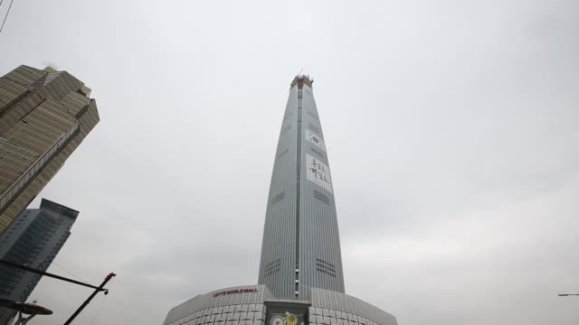 Vehicles drive past the Lotte Corp World Tower under construction in Seoul South Korea on Thursday Dec 10 Signage for the Lotte Corp World Mall is...
