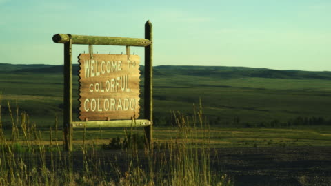 """vehicles drive past the """"welcome to colorful colorado"""" state line sign on the colorado/wyoming border at sunset - welcome sign stock videos & royalty-free footage"""