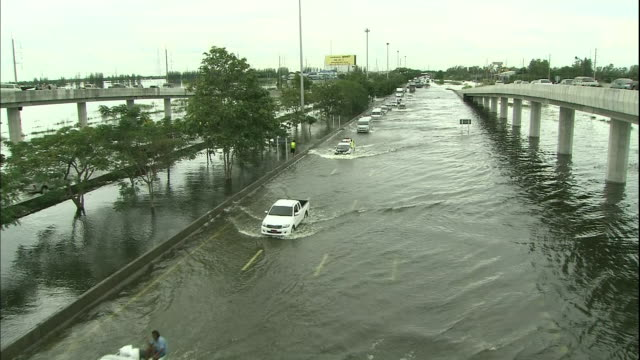 Vehicles drive slowly on a flooded highway in Thailand