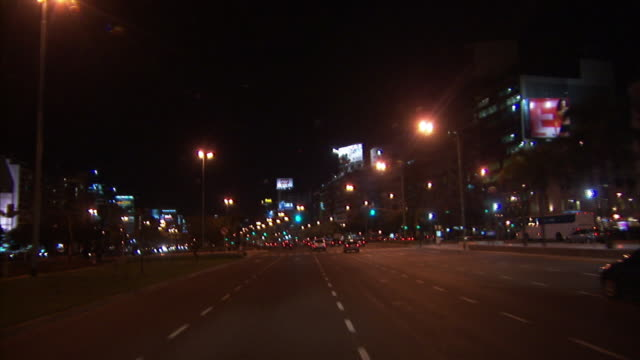 Vehicles drive through busy streets in Buenos Aires at night.