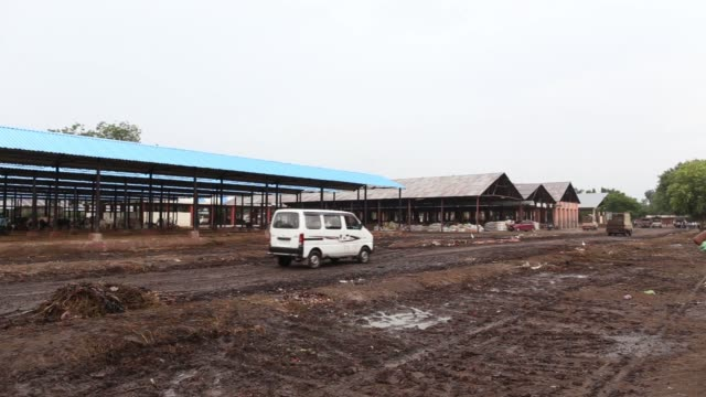 Vehicles drive through the Agricultural Produce Market Committee wholesale market in Dhule district Maharashtra India on Tuesday Oct 10 Vehicles sit...