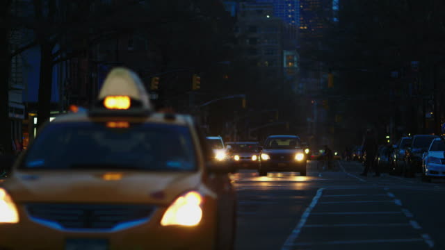 vídeos de stock e filmes b-roll de ws vehicles driving and pedestrians walking through the street at night / new york city, new york, united states - formato letterbox
