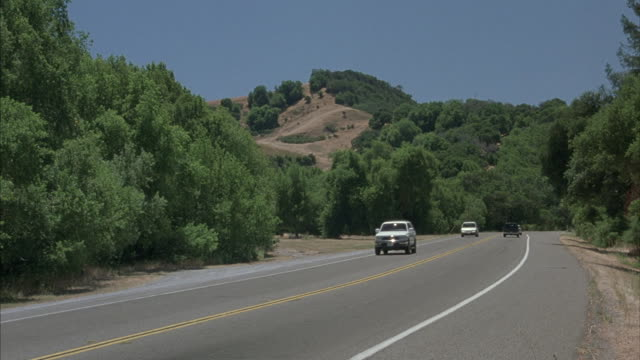 Vehicles driving in both directions on a two-lane mountain highway.