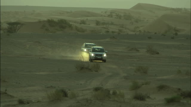 vehicles driving in desert, jordan - sports utility vehicle stock-videos und b-roll-filmmaterial