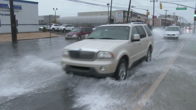 Vehicles Driving On Flooded Streets