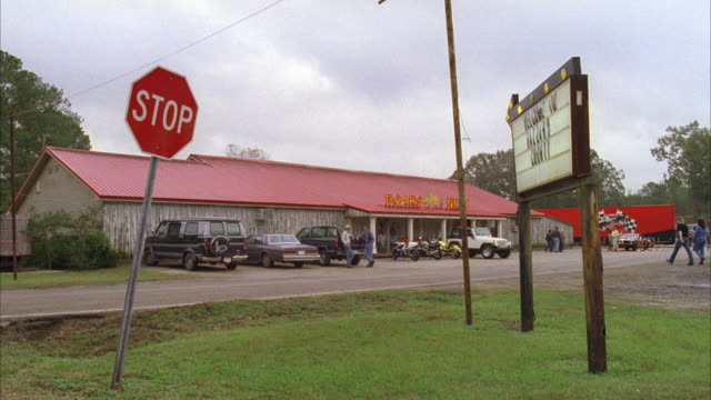 MS Vehicles entering and parked in front of small red roof rural diner