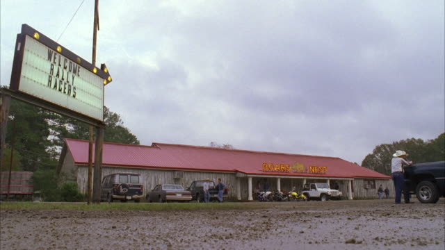 vídeos de stock, filmes e b-roll de ms vehicles entering and parked in front of small red roof rural diner - lanchonete