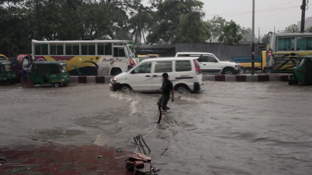 vídeos de stock, filmes e b-roll de vehicles floundering in the water during a tropical monsoon rain and flooding in chittagong, chittagong, bangladesh, indian sub-continent, asia - bangladesh