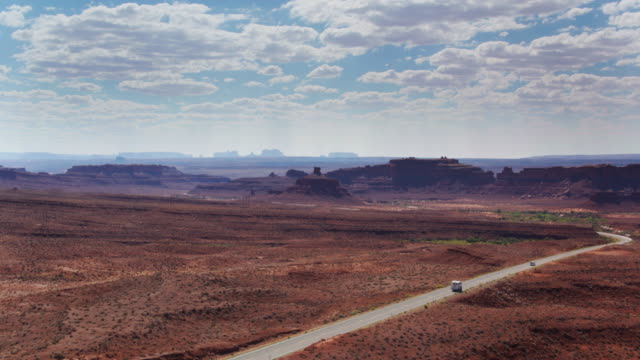 vehicles heading into monument valley - drone shot - southwest usa video stock e b–roll