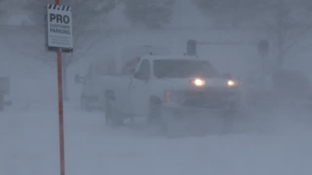 Vehicles in a parking lot in Brewster New York are barely visible as strong winds combine with heavy snow to create near whiteout conditions during...
