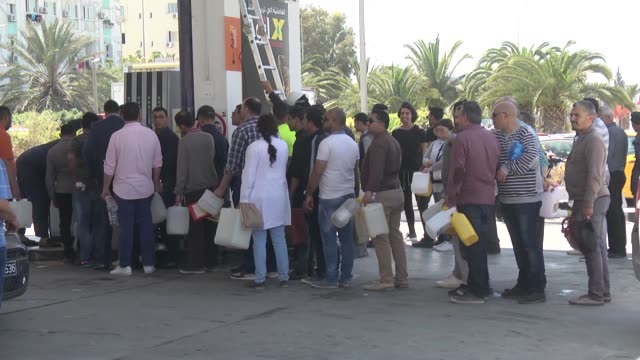 vehicles line up for gasoline and people wait in queue to fill empty containers at a gas station as tunisian fuel workers go on a three-day strike to... - crisis stock videos & royalty-free footage