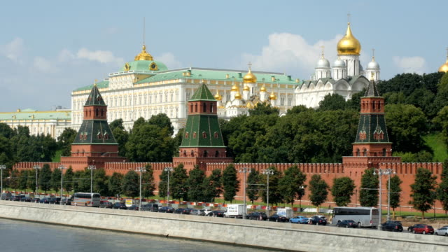 vehicles move down street past kremlin wall, along moskva river/ moscow, russia - 赤の広場点の映像素材/bロール