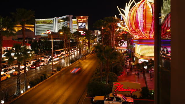 vehicles move on the las vegas strip near caesar's palace as gamblers move in and out of casinos. - the strip las vegas stock videos & royalty-free footage