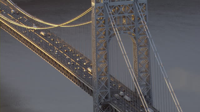 Vehicles move over the decks of the George Washington Bridge in New York City at golden hour.
