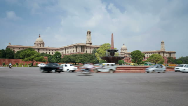 vehicles move through a roundabout on the raj path in front of india's parliament building. - parliament building stock videos & royalty-free footage